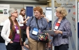 Johanna Bos, Janis Summers, and Susan Stack visit in the Exhibit Hall.