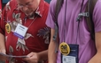 Glenn Mack and Hunter Badgley review information for the prayer walk at GA 220.