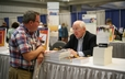 Author Joe Small chats with a visitor during a booksigning at the 220th GA Exhibit Hall.
